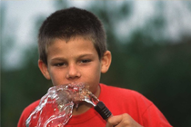 Picture of a child drinking from a garden hose